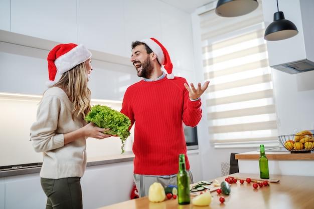 Casal alegre, preparando o jantar saudável para a véspera de natal