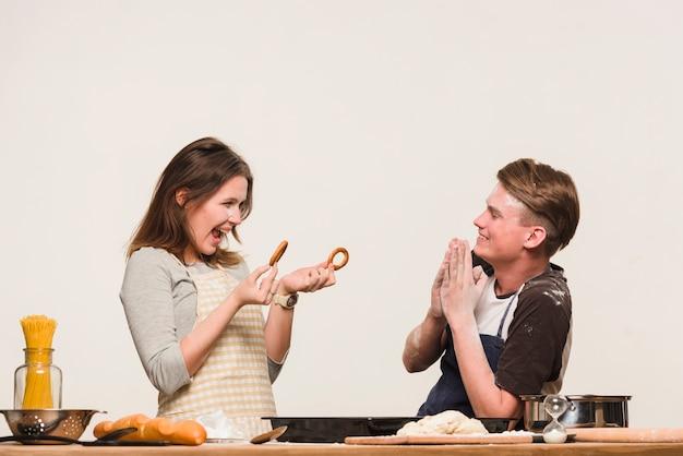 Casal alegre preparando pastelaria e se divertindo