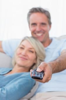 Casal alegre relaxando em casa assistindo tv