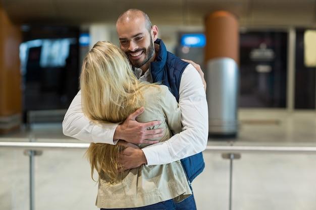 Casal alegre se abraçando na sala de espera