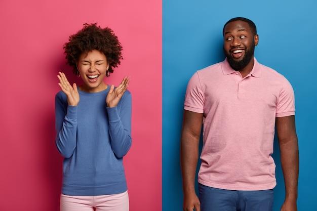 Casal alegre se diverte, ri enquanto assiste filme hilário, gosta de comédia, mulher cacheada não para de rir, levanta as palmas das mãos