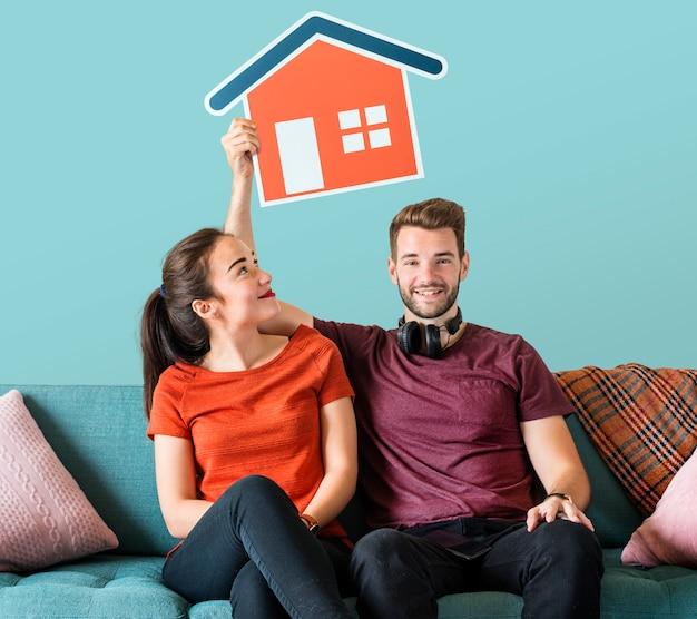 Casal alegre segurando um ícone de casa