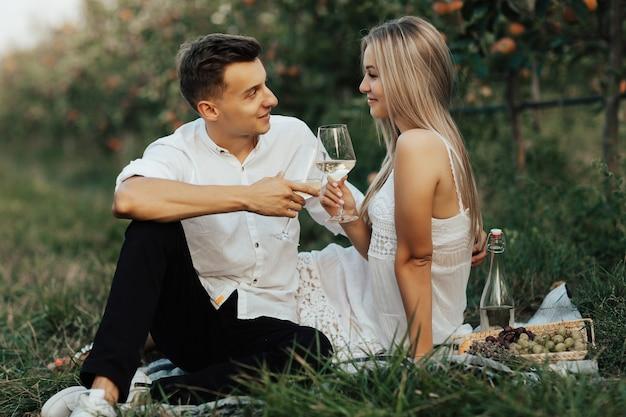 Casal alegre tilintando de copos com vinho branco enquanto está sentado no cobertor. tinir de taças de vinho durante um encontro romântico ao ar livre.