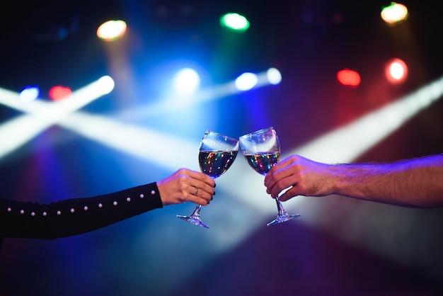 Casal alegre tilintar copos de champanhe na festa