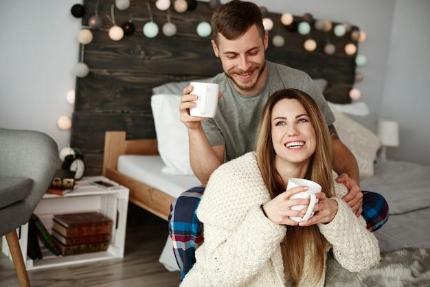 Casal alegre tomando café no quarto