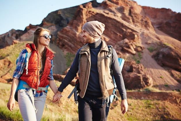 Casal alegre turista tendo caminhada