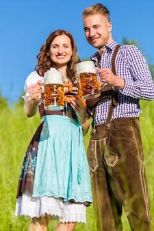 Casal alemão em tracht com cerveja e pretzel