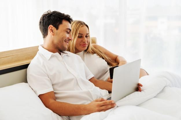 Casal amante caucasiano desfrutar com mídias sociais juntos no laptop juntos no quarto de manhã cedo