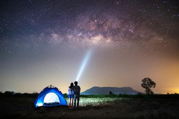 Casal amante em pé perto da tenda e olhando a via láctea e estrelas