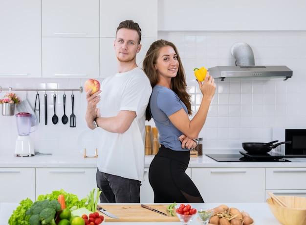 Casal amante feliz cozinhando juntos na cozinha. jovem e mulher em pé, segurando frutas e vegetais frescos nas mãos