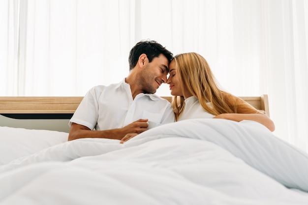 Casal amante vestindo branco sorrindo feliz jogando juntos na cama de manhã cedo