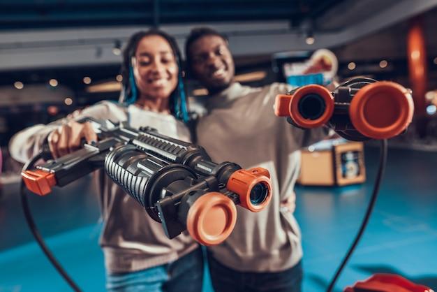Casal americano africano com armas no fliperama.