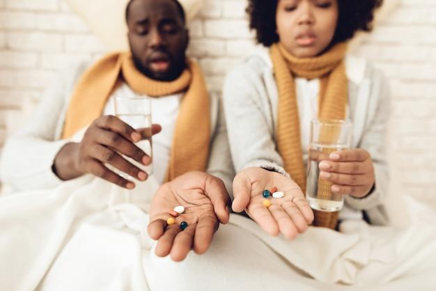 Casal americano africano doente bebe comprimidos.