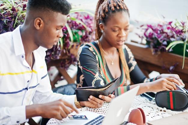 Casal americano africano elegante bonito sentado no café ao ar livre com laptop com cartão de crédito e dinheiro da carteira.