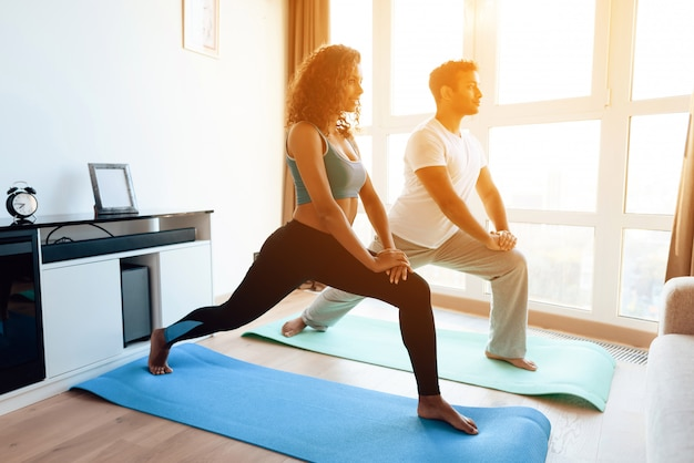 Casal americano africano fazendo exercícios de ioga em casa