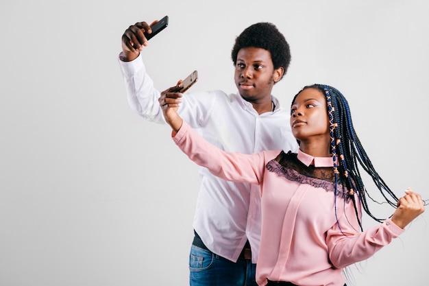 Casal americano africano feliz tendo selfie com smartphone no estúdio branco