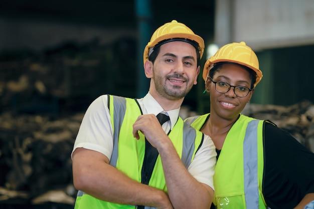 Casal amigo team worker mix raça gosta de trabalhar em uma fábrica pesada juntos, felizes, sorrindo, retrato, olhando a câmera