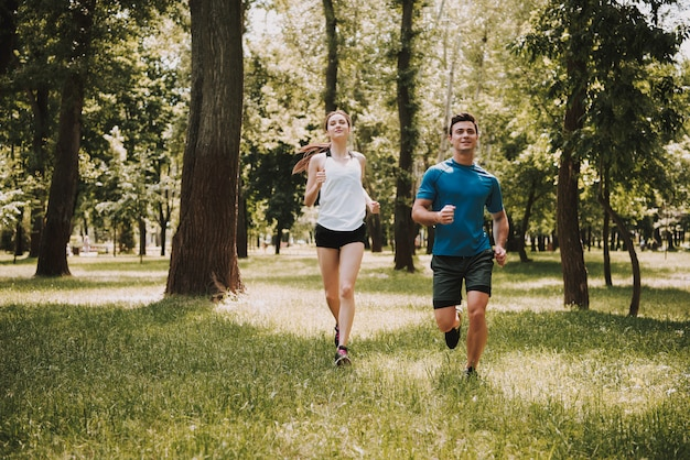Casal amor de atletas está correndo no parque verde