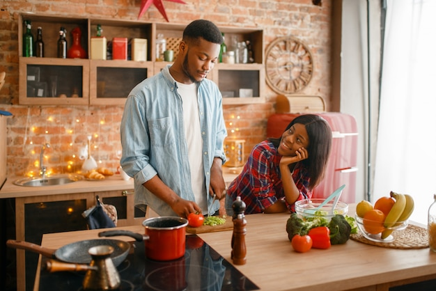 Casal amor negro cozinhando um jantar romântico na cozinha. família africana preparando salada de legumes em casa. estilo de vida vegetariano saudável