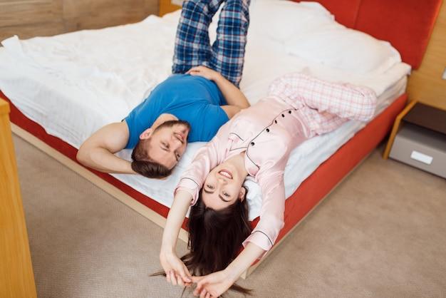Casal amor romântico de pijama, deitado na cama em casa, bom dia. relacionamento harmonioso na jovem família.