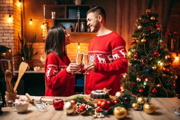 Casal amor segura taças com champanhe, romântica celebração de natal. homem e mulher celebram o natal juntos