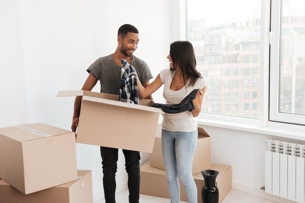 Casal amoroso alegre em pé perto de caixas desempacotadas. olhem uns para os outros. homem segurando a caixa com roupas.