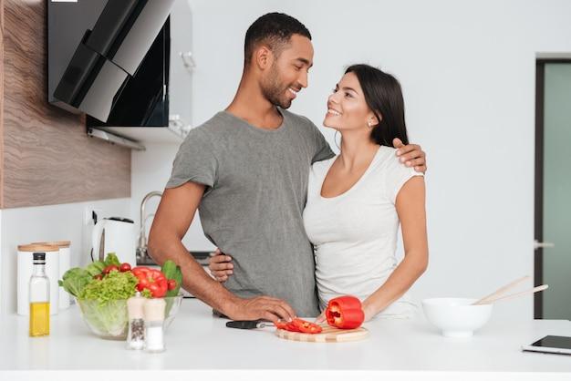 Casal amoroso alegre na cozinha se abraçando enquanto cozinha. olhem uns para os outros.