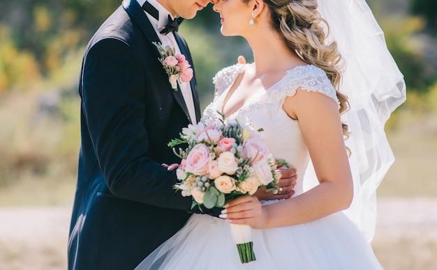 Casal amoroso de mãos dadas com anéis contra o vestido de noiva