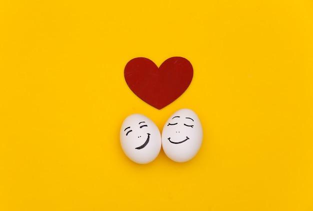 Casal amoroso feliz de ovos de galinha enfrenta com coração em fundo amarelo
