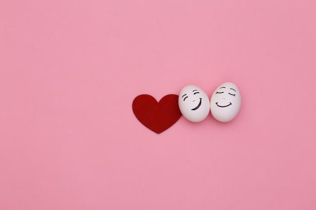 Casal amoroso feliz de rostos e coração de ovos de galinha em fundo rosa