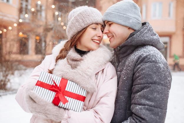 Casal amoroso feliz lá fora no parque de inverno nevado, segurando um presente com uma fita vermelha nas mãos. homem alegre e mulher comemorando o dia dos namorados juntos. encontro em um dia frio de inverno lá fora.