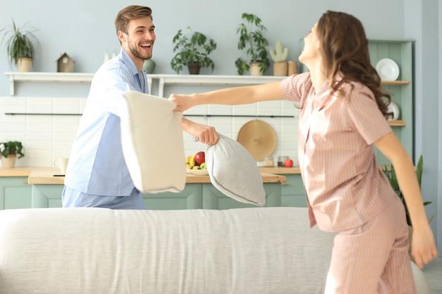 Casal amoroso feliz se divertindo enquanto tinha uma luta de travesseiros na sala de estar.