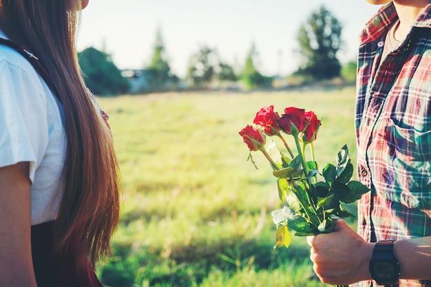 Casal amoroso - homem com rosa esperando sua mulher no parque.