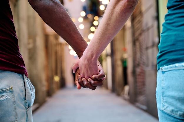 Casal amoroso inter-racial de mãos dadas em local ao ar livre - conceito multiétnico