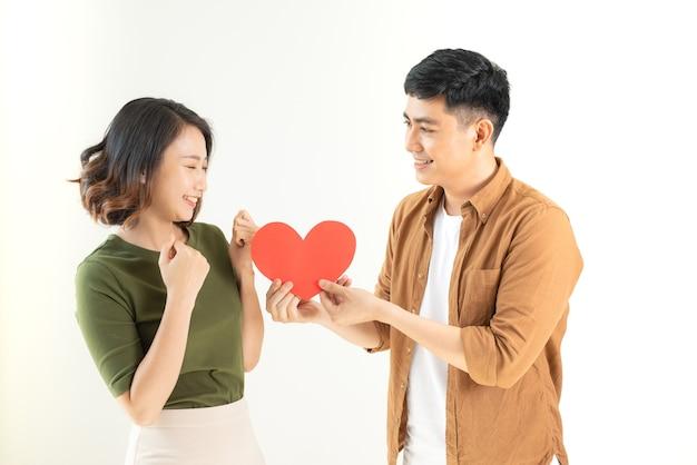Casal amoroso sorridente segurando forma de coração sobre uma parede branca.