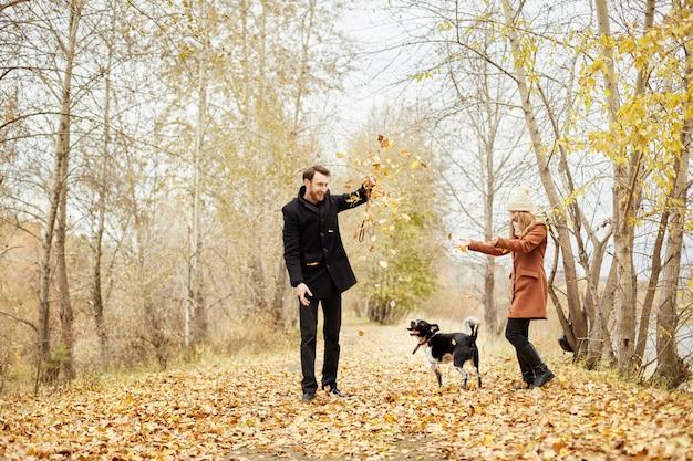 Casal andando com o cão no parque e abraçando
