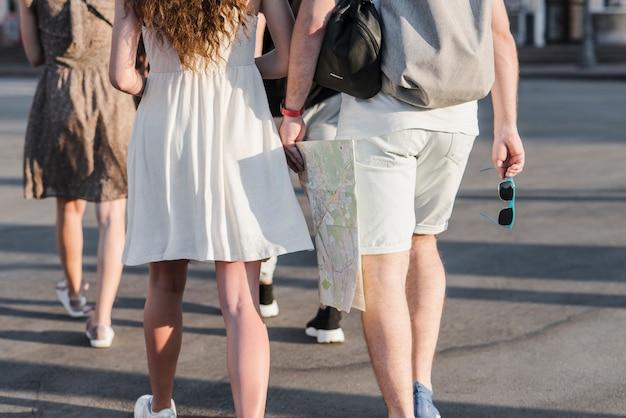 Casal andando com o mapa na rua