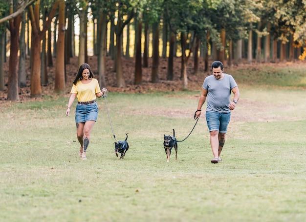Casal andando com seu cachorro na coleira em um parque. homem e mulher, cada um levando um cachorro para passear no parque em um dia ensolarado.