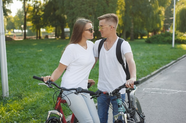 Casal andando de bicicleta na cidade de verão