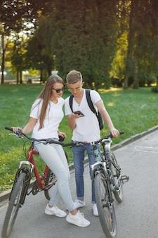 Casal andando de bicicleta na floresta de verão
