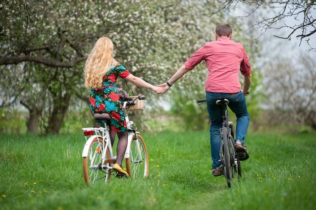 Casal andando de bicicleta no jardim primavera
