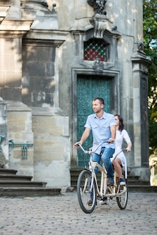 Casal andando de bicicleta tandem retrô