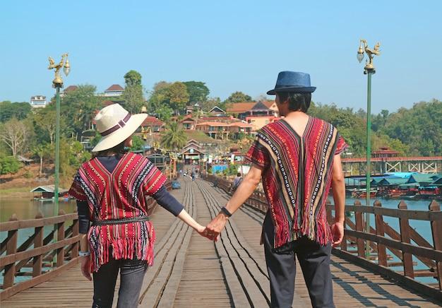 Casal andando de mãos dadas na ponte de mon ou saphan mon, o ponto de referência de sangkhlaburi, tailândia