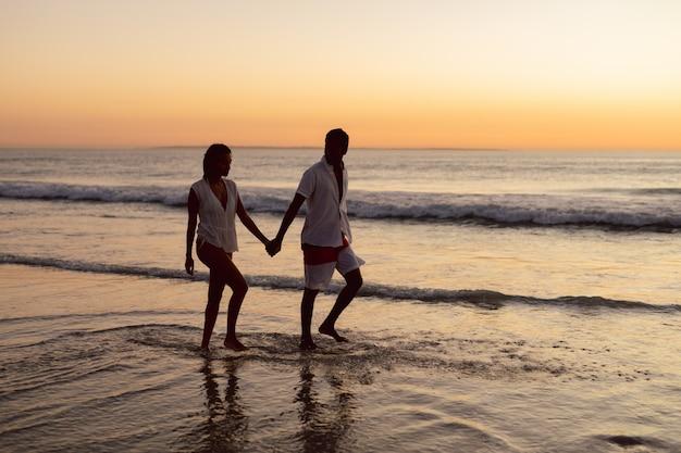 Casal andando de mãos dadas na praia