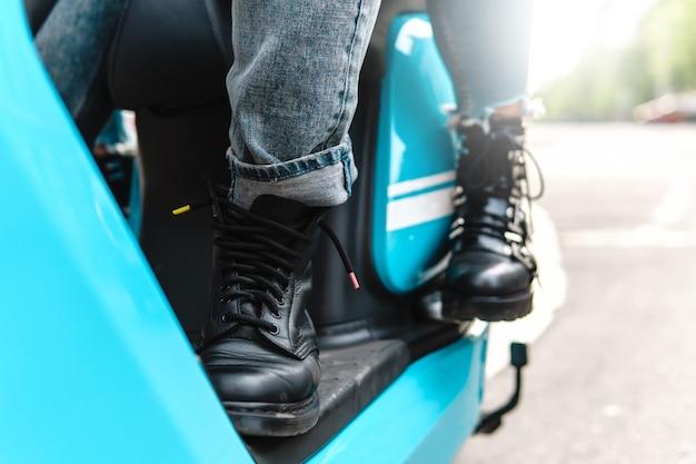 Casal andando de moto. close do corpo e das pernas de uma scooter usando botas