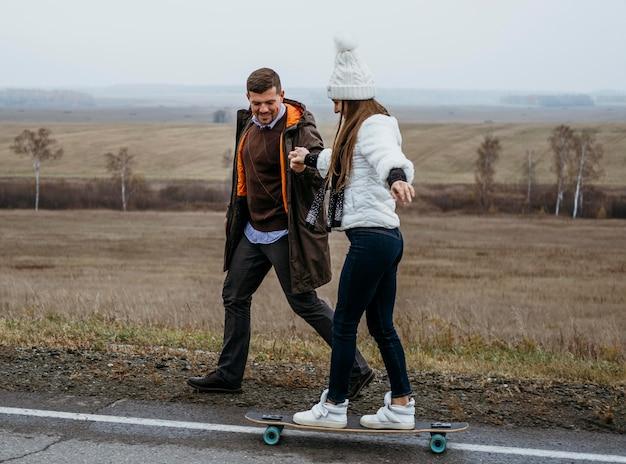 Casal andando de skate ao ar livre na estrada