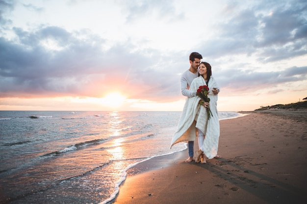 Casal andando na praia com um buquê de rosas ao pôr do sol