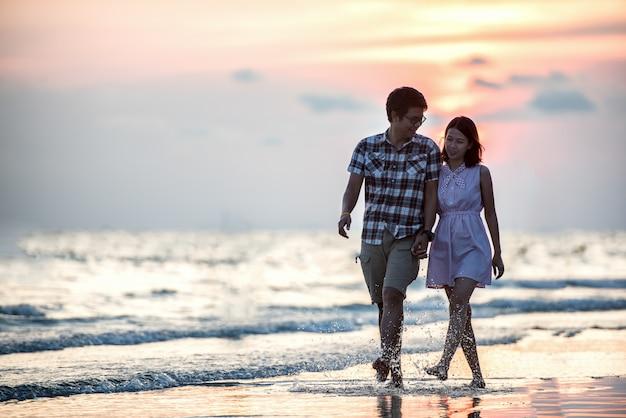 Casal andando na praia. jovem, feliz, par interracial, andar praia, sorrindo, segurando, ao redor, cada