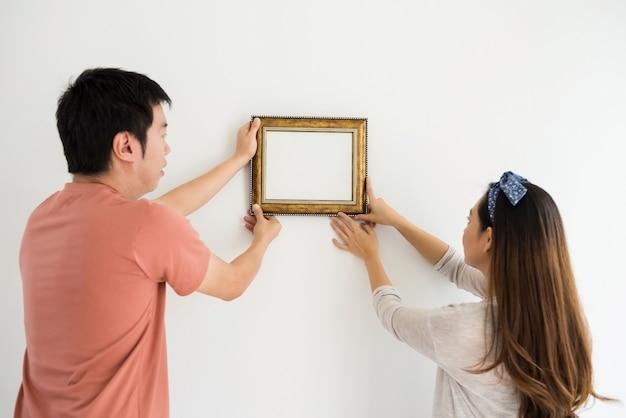 Casal anexar moldura na casa nova