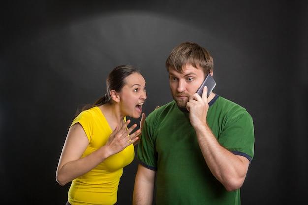 Casal animado brincando com um celular
